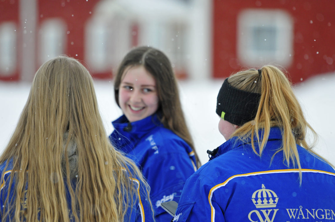 Elever ute om vintern. Två st ser vi ryggen på men den tredje går lite framför och vänder sig om och ler mot sina vänner.