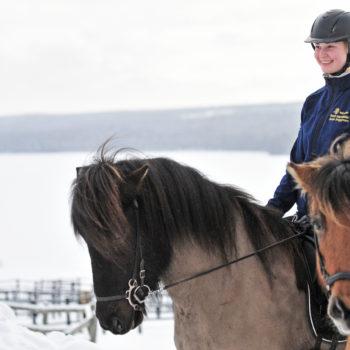 Elev i hjälm och jacka med wångensigill på bröstet sitter på en islandshäst. I bakgrunden syns ett snöttäckt vinterlandskap