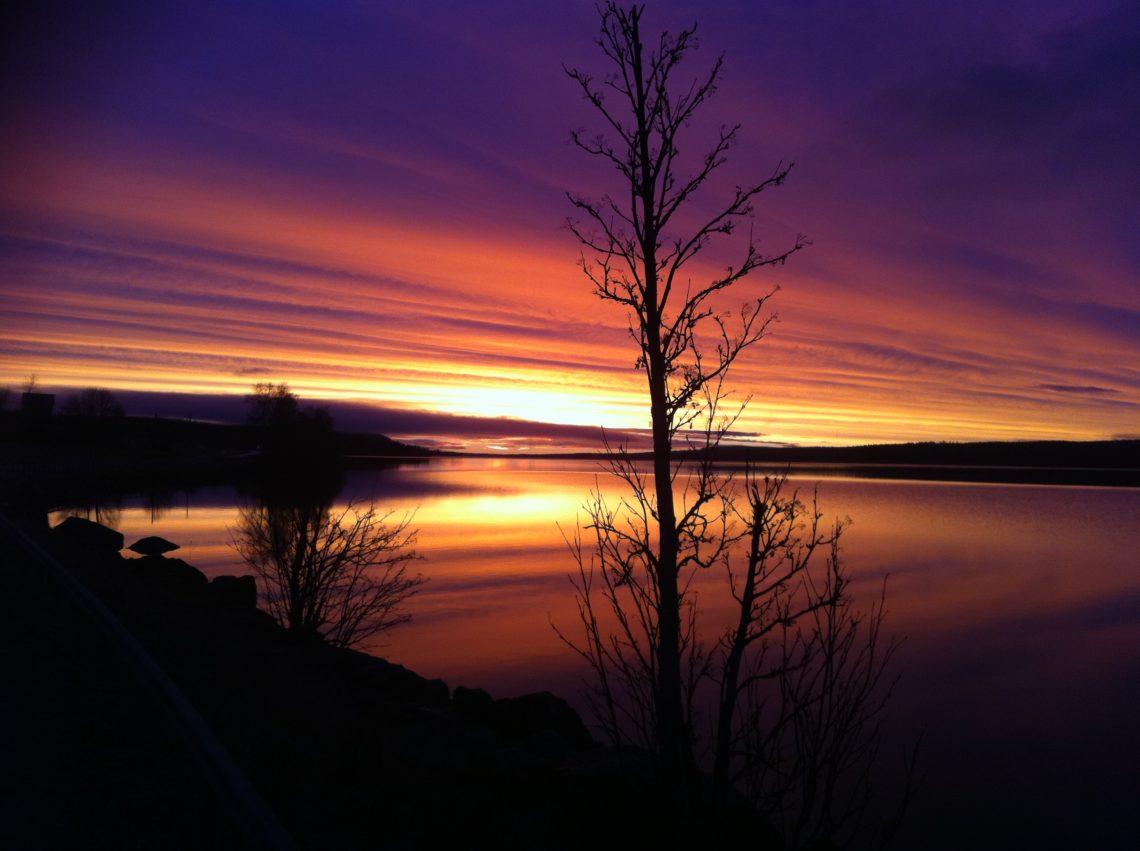Soluppgång över Alsensjön i gulröda och lila färger. Alsensjön passerar du längs S:t Olavsleden