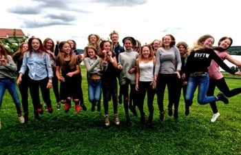 Femton glada deltagare på islandhästlägret på gräsmattan hoppar unsiont upp i luften