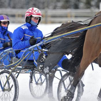 Två travekipage från Wångens travgymnasium i snötäckt vinterlandskap. Elever i blåa Wångentravdressar kör varmblod på Wångens travbana