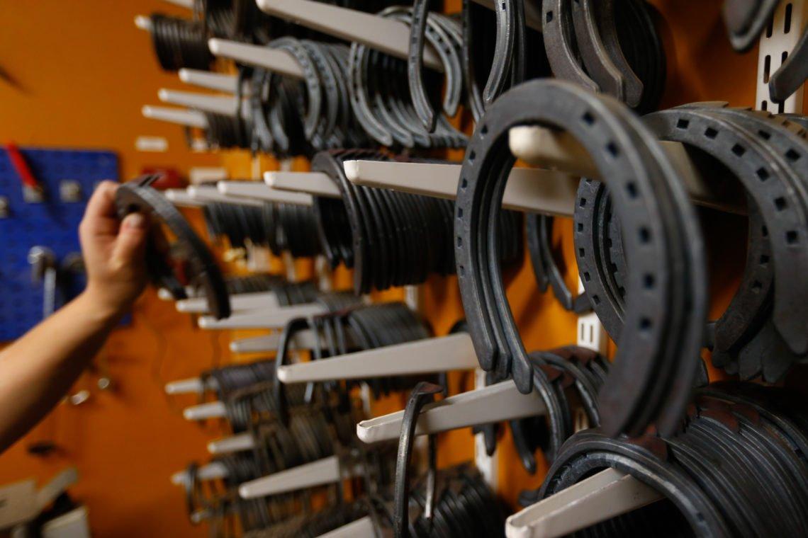Hel vägg med hästskor i rader på krokar för tilläggsutibldningen till hovslagare