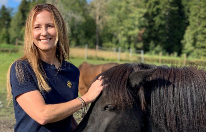 Emma Roos står i hästhage och klappar på islandshäst