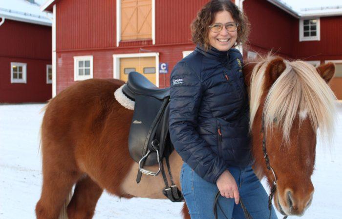 Joanna står med armen om en sadlad islandhäst framför ett av Wången stall