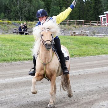 Ryttare på gör segergest med ena handen i luften när de kommer över mållinjen.