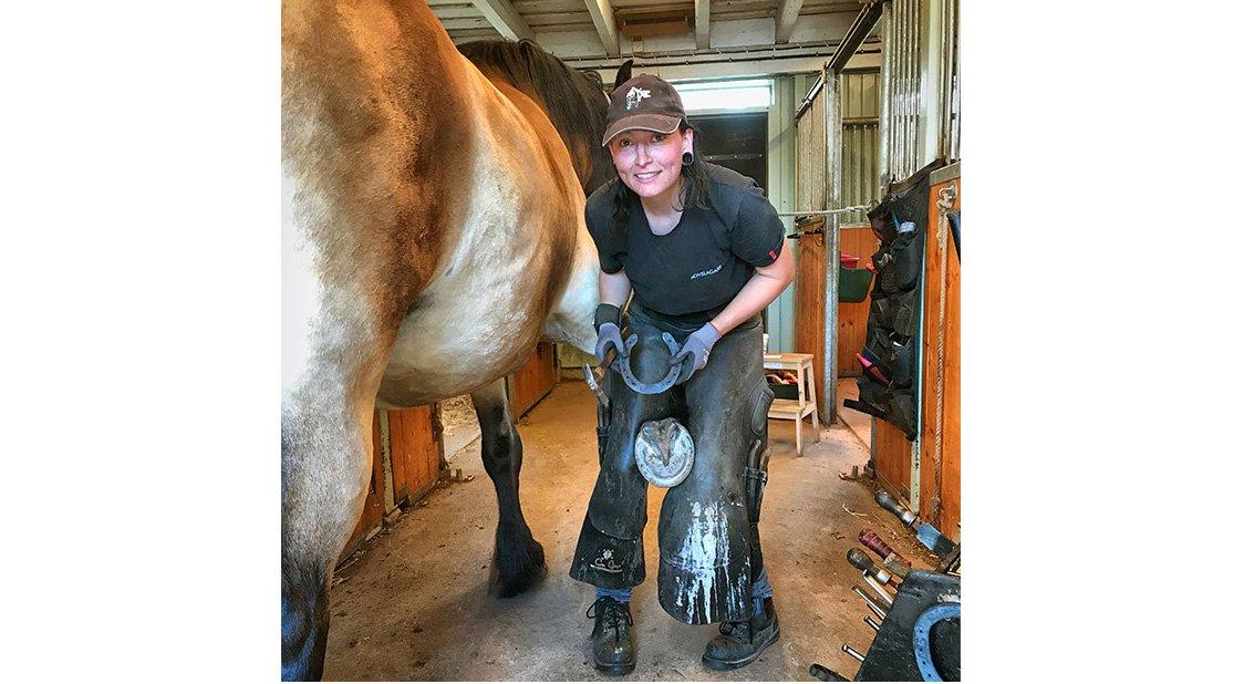 Hovslagare Zola Runsten i stallgång tittar in i kameran med en hästsko i handen i full färd med att sko en stor brukshäst