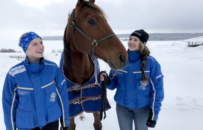 I blå Wångenjackor står Emmie och Lovisa på varsin sida om en brun häst i blått täcke, bakom dem ett vitt vinterlandskap.