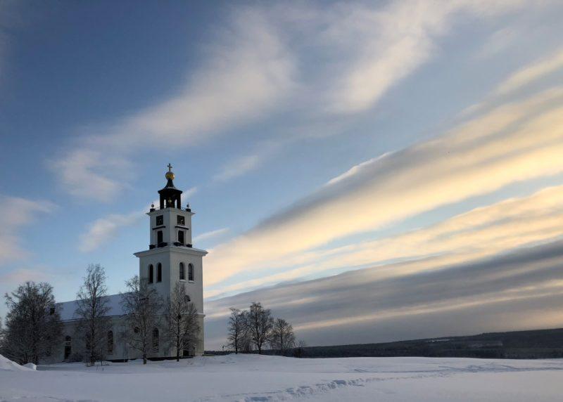 Alsens vita kyrka med dramatiska moln som streck över himlen. Marken är täckt av snö.