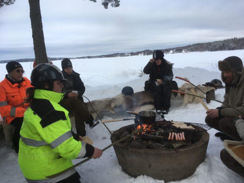 I varseljackor och hjälm sitter eleverna runt elden. I bakgrunden en frusen sjö.