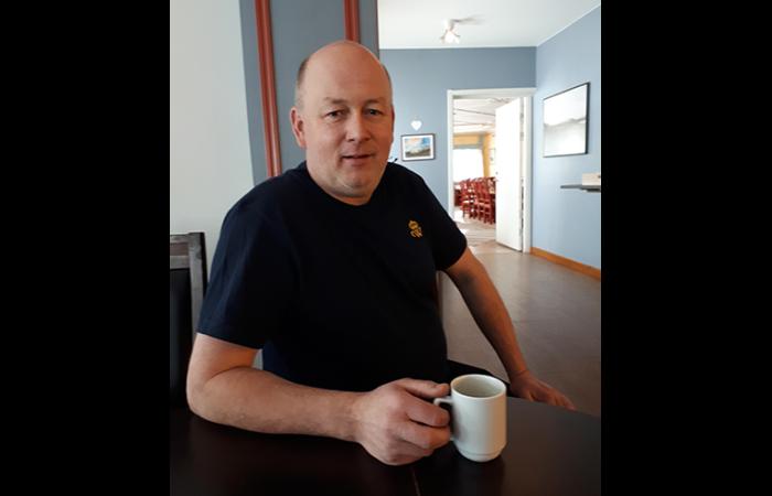 Kåre på besök på Wången i sitt uppdrag för kuskutbildningen i brukshästkörning. Här sitter han vid ett bord på Wångens wärdshus med en kaffekopp framför sig.