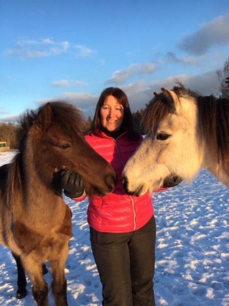 Hippolog Annika Larelius mellan två hästar i en hage
