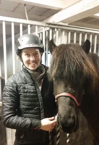 Hippolog Sara Liedberg med hjälm på bredvid en islandhäst i stallgången