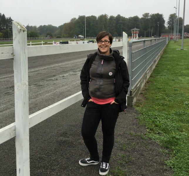 Hippolog Elin Westerlund bredvid högt vitt staket intill en travbana