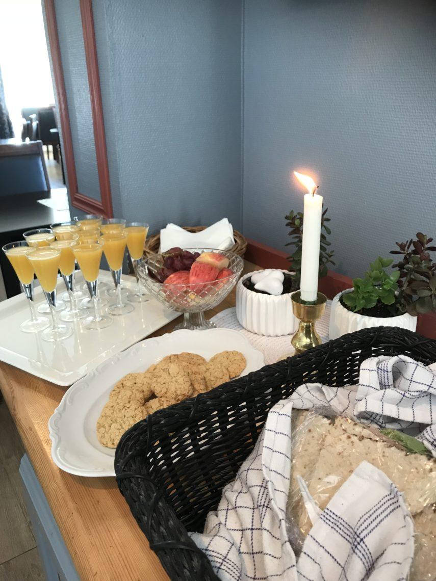 Bord uppdukat med juice i shotsglas och tunnbrödssmörgåsar, ett levande ljus och ett kakfat