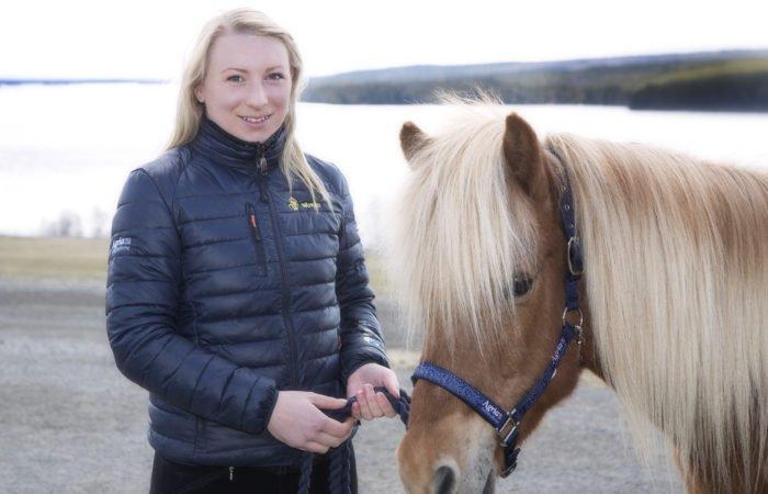 Sara står brevid en islandshäst i grimma med Alsensjön i bakgrunden