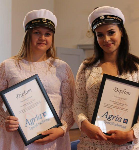 Två stipendiater i kyrkan, klädda i vitt, håller i varsitt inramat diplom med Agrias logotyp.