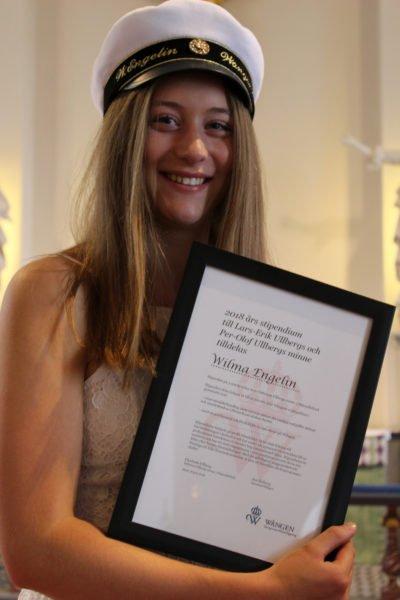 Stipendiaten iförd studentmössa håller i sitt inramade diplom
