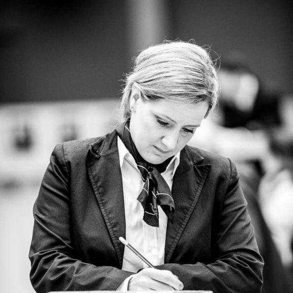 Svartvit bild på kvinna i kavaj som sitter vid ett bord. Med en penna i handen tittar hon koncentrerat ned och antecknar.