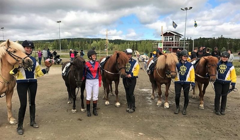 Ryttare i tävlingsdressar står uppställda brevid sina hästar utanför travbanan