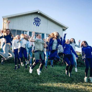 15 glada tjejer på en grön gräsmatta hoppar upp i luften. Alla deltagare på 2018-års islandshästridläger