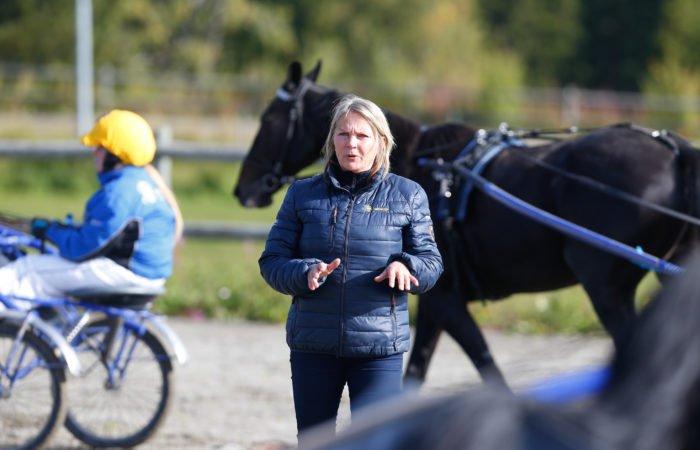 Hästlärare instruerar travelever på körbana utomhus