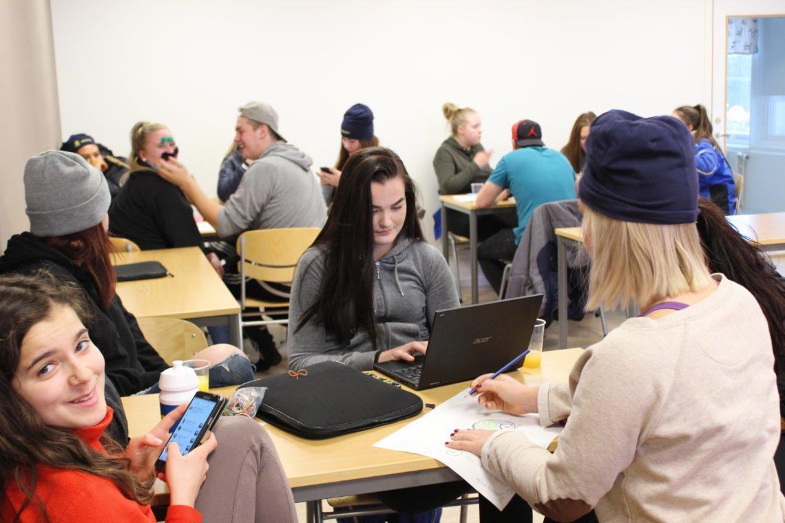 Elever i klassrum. En framför en dator, en upptagen med mobilen, en skriver på papper, medan två i bakgrunden leker med inspirationsmaterialet och skapar mustacher till varann.