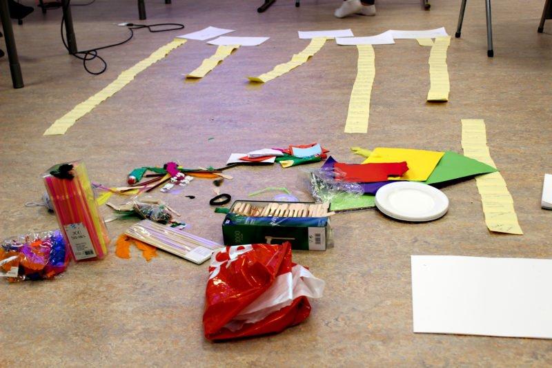 Ett klassrums golv med gula post-it-lappar klistrade i fyra långa rader samt en mängd attiraljer för att främja tankearbetet o kreativiteten som färgglada papper, glasspinnar, papperstallrikar och dekorationer.