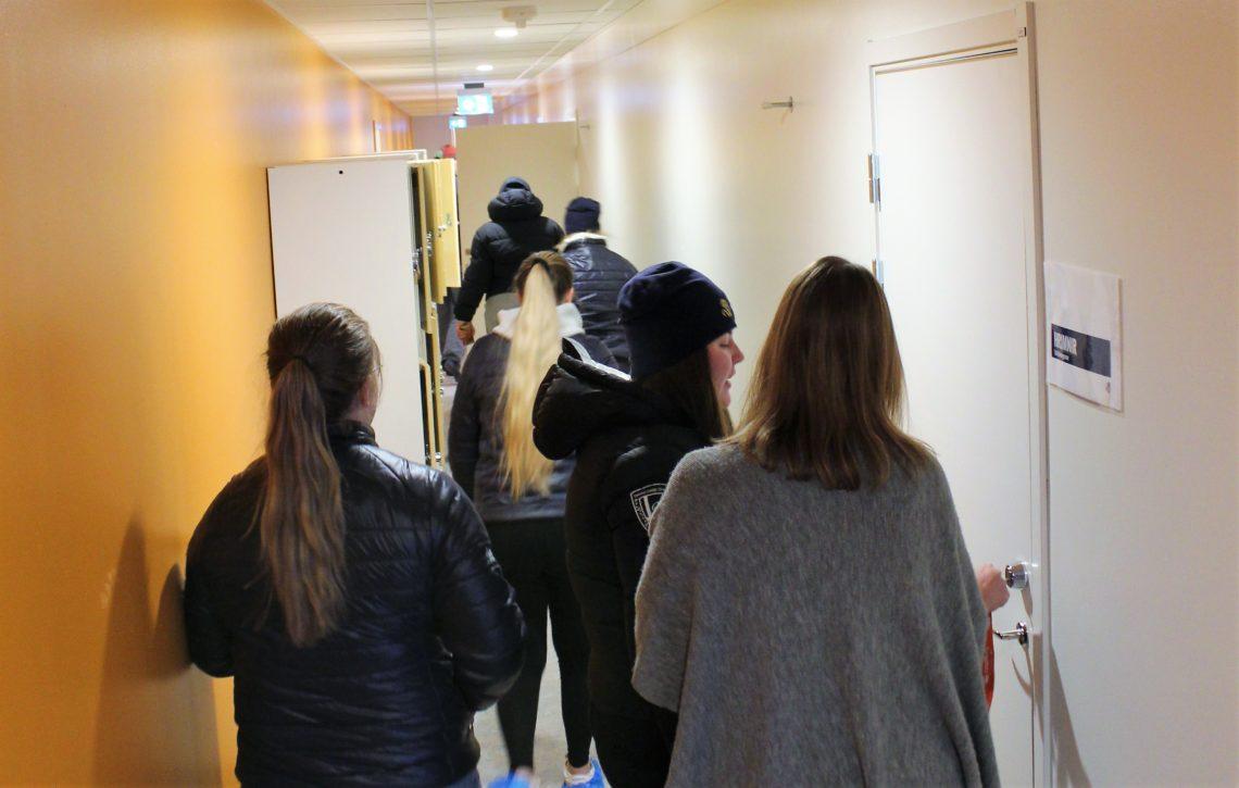 Gymnasieelever och lärare i skolkorridor
