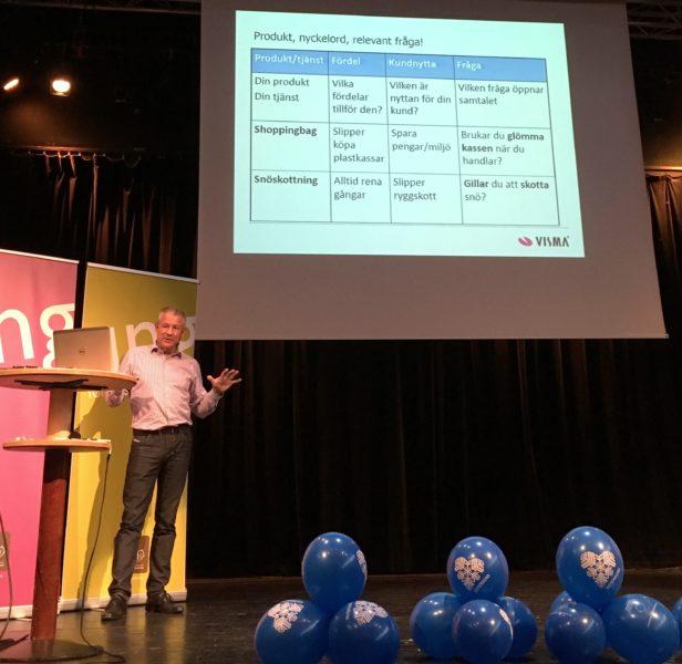 Man på scen talar till en powerpointbild med säljtips i matrisform.