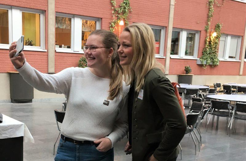 Ung tjej håller i mobilkamera och tar selfie tillsammans med en företagarrepresentant