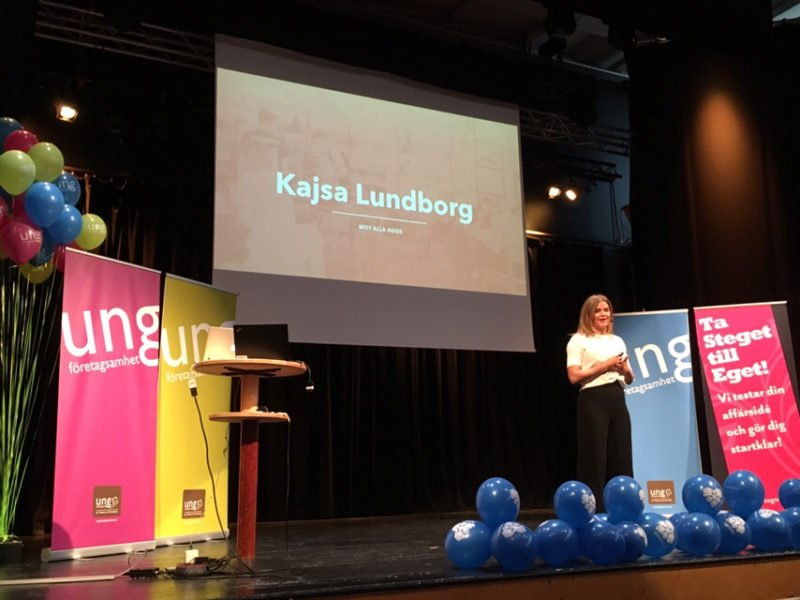 Ung kvinna på scen med texten Kajsa Lundborg stort på skärmen. Roll-ups med texten Ung Företagsamhet och ballonger syns också