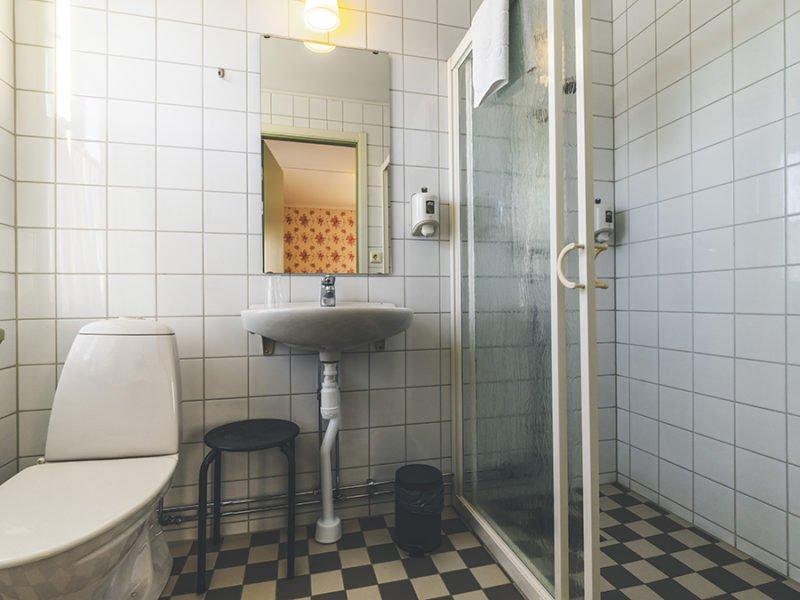 Boendet har wc och dusch med skjutdörr. Helkalklat med vita väggar och svartvittrutigt golv