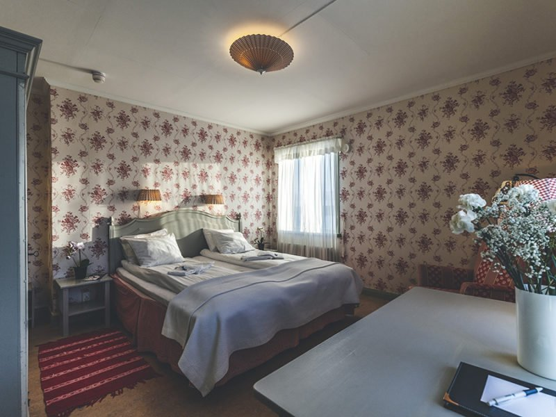Hotellrum med dubbelsäng och vitröda tapeter. I förgrunden syns ett skrivbord.
