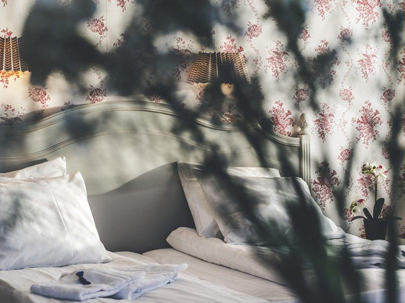 Närbild på bäddad säng med grå snidad trägavel i bröllopssviten