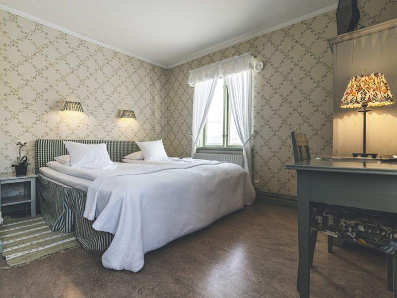 Dubbelsäng i ett rum med gröna gammeldags tapeter, vita skria gardiner för fönstren. Ett grön skrivbord i trä skymtar i förgrunden