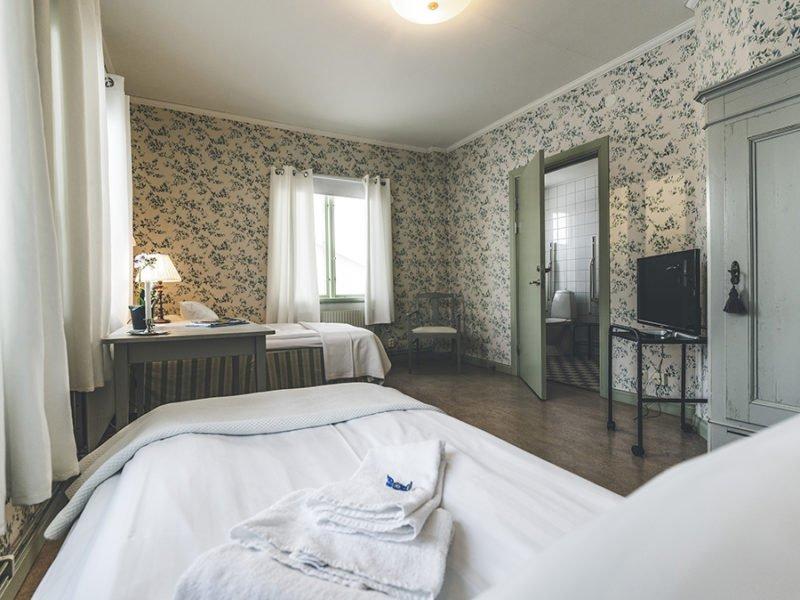 Boende i dubbelrum med två enkelsängar utplacerade i ett stort rum med skrivbord emellan. Fönster på två sidor och egen toalett