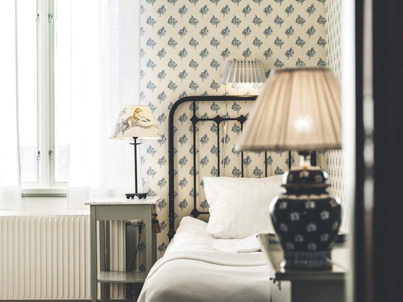 Boende i rum i gammeldags stil. Sänggavel i svart järn. Blåblommig tapet