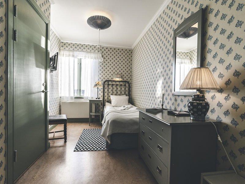 Boende i litet enkelrum med järnsäng, byrå, spegel och målade trämöbler. Ett fönster och ingång till egen toalett och dusch