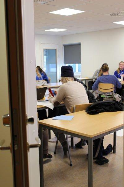 Genom en halvöppen dörr ser man in i ett klassrum där elever sitter under en lektion.