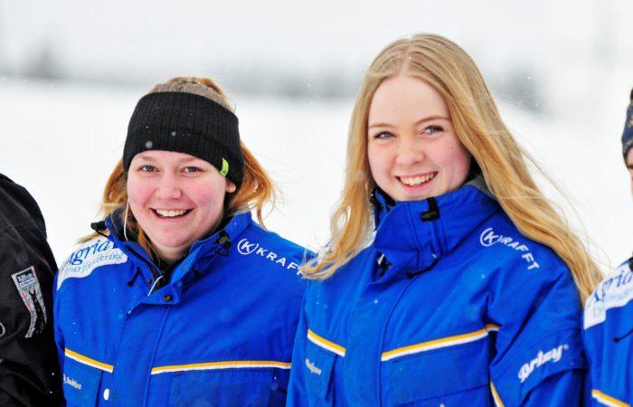 Två gymnasielever utomhus i vinterväder iklädda Wångens blå travdressar.