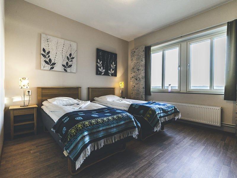 Hotellrum med två enkelsängar, gavlarna i trä och filtar över sängändarna. Parkettgolv och två dubbelfönster.
