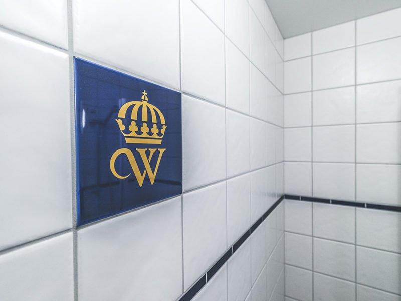 Detaljbild från hotellrummens badrum. Vit kakelvägg där en kakelplatta sticker ut - den är blå med Wångens gula sigill, ett W med krona ovanpå