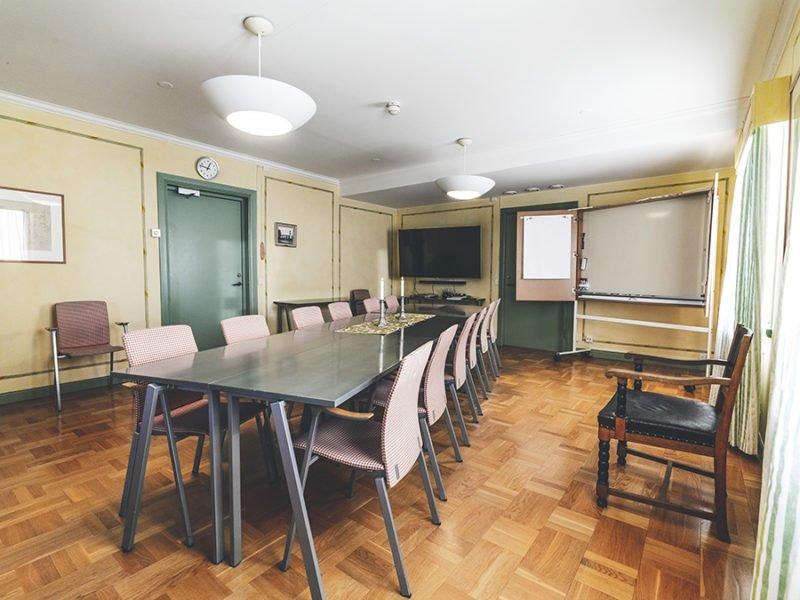 Vy över rum med konferensrum med sex stolar på vardera sida. Stolarna är klädda i rödvitrutigt tyg. längst bort finns en whiteboardtavla att skriva på och en tv-skärm att koppla dator mot