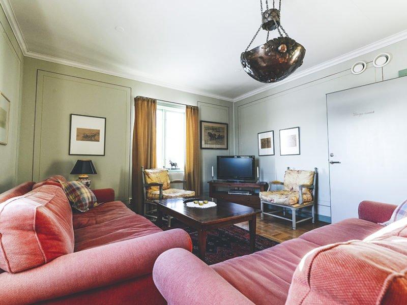 Vy över sällskapsrum med två stora soffor, soffbord, stoppade fotåljer och en tv.