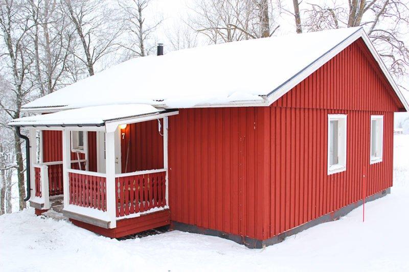 röd stuga i snö. Stugor är en av alla typer av boende som vi har