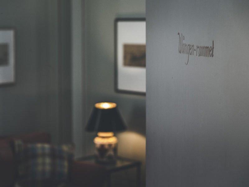 Dörr på glänt. På dörren står målat med snirklig stil Wångenrummet