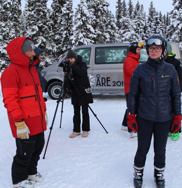 Henrik Windstedt i profil bakom honom en reporter från TVÅRe som tittar in i filmkamera på stativ. I bakgrunden syns en minibuss från Åre2019 snöiga granar, och åkaren Alexander Ryden med mössa och googles på huvudet. Framför honom står hippologstudenten Josefin Löfman.
