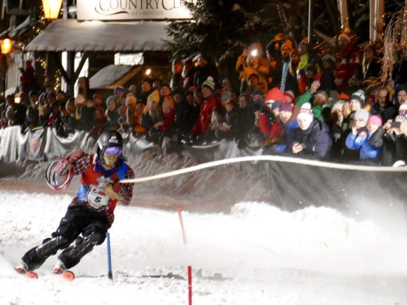 Skidåkare tar sväng runt en port. Repet är sträckt framför honom i luften. Hästen är redan ur bild. I bakgrunden syns den hejande publiken