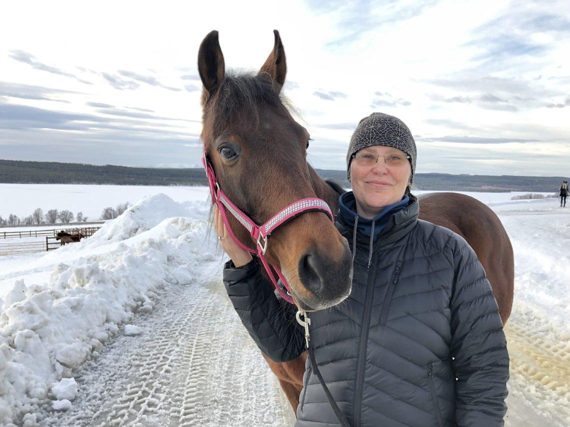 Lena går hästskötarkursen. Här står hon klädd i vinterjacka och mössa står bredvid en varmblodstravare i rosa strassbeklädd grimma i ett vintrigt landskap