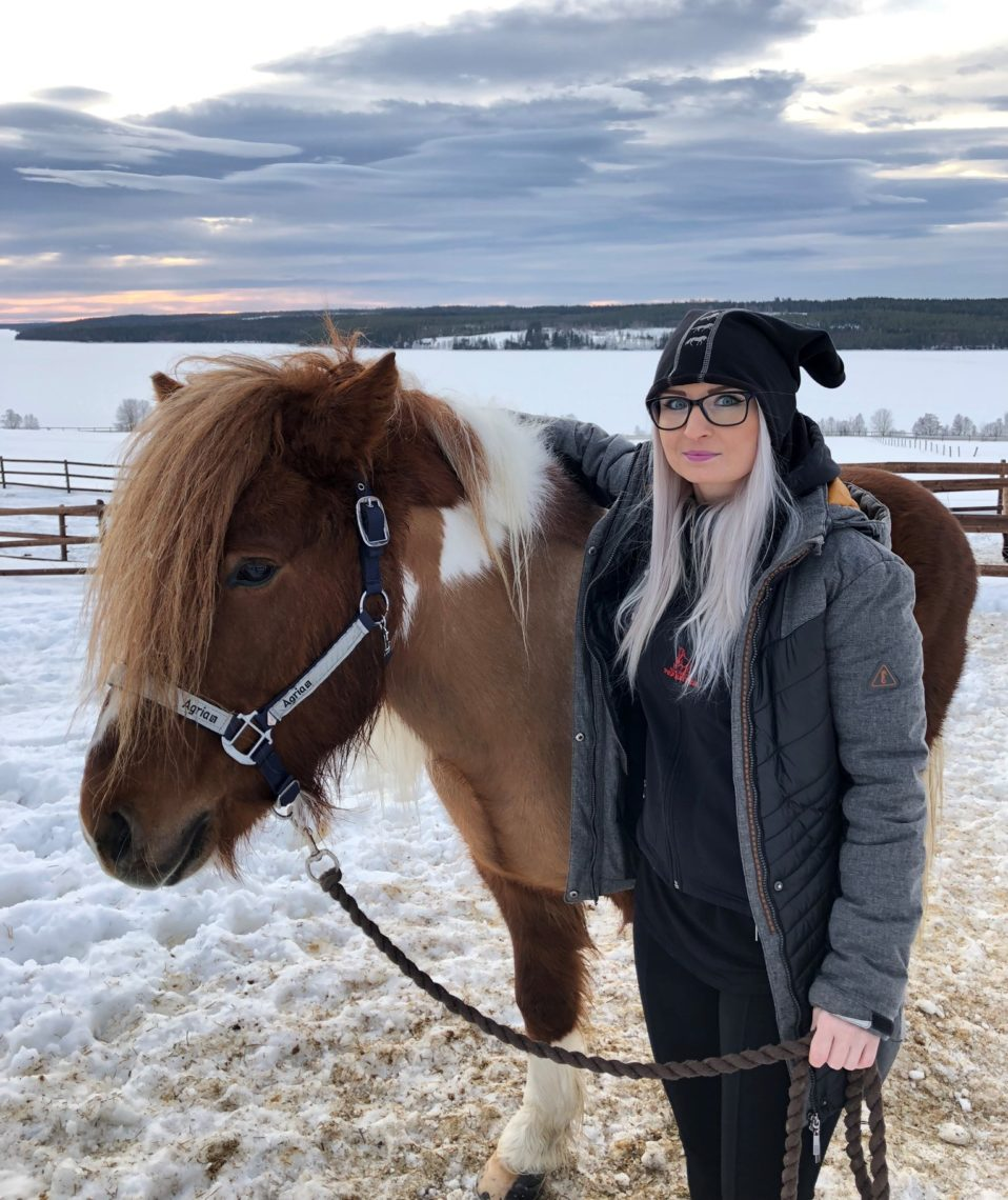 Islandshäst brunvit skäck i snötäckt hage. Hästen har en reflexgrimma som det står Agria på. I grimskaftet håller Madeleine som läser på Allmän kurs häst. Hon har en arm över hästens hals och vänstern håller hon i hon grimskaftet.
